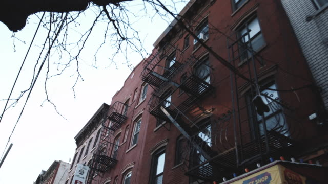 wide angle shot of an anonymous apartment building in new york city - fire escape stock videos & royalty-free footage