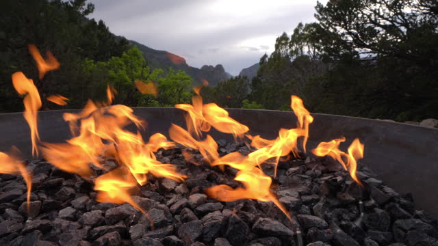 wide angle shot of an outdoor cast iron gas fire pit with a view of thimble rock point in unaweep canyon in western colorado - modern rock stock videos & royalty-free footage
