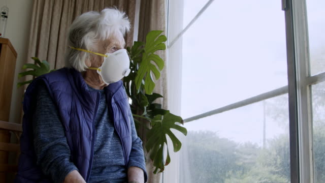 wide angle shot of distraught elderly senior caucasian woman looking out the window feeling loneliness wearing an n95 protective face mask to prevent the spread of covid sars ncov 19 coronavirus swine flu h7n9 influenza illness during cold and flu season - senior women stock videos & royalty-free footage