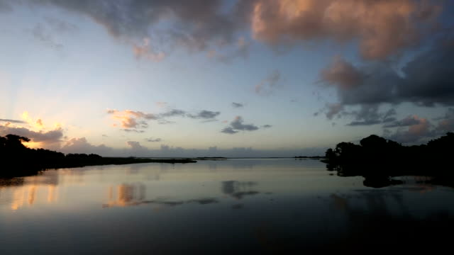Wide angle shot of dramatic sunrise over calm lake water shot from boat.