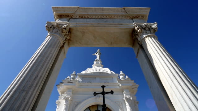 Wide angle shot of marble columns and black cross in old cemetery.