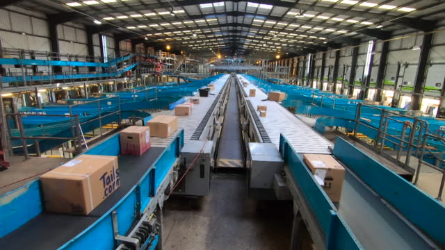 wide angle shot of parcels and boxes on conveyor belt at yodel delivery sorting centre hatfield - production line stock videos & royalty-free footage