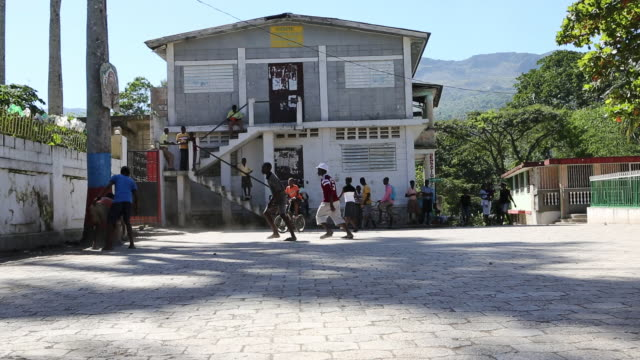 a wide angle shot of plenty of children who are playing basketball on a schoolyard in front of a schoolhouse in a poor neighbourhood in pilate haiti - 分校点の映像素材/bロール