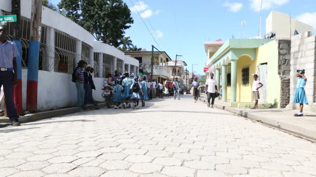 a wide angle shot of several young school girls in blue uniforms as they are walking down a busy street in pilate haiti while a young man on a moped... - hispaniola stock videos and b-roll footage