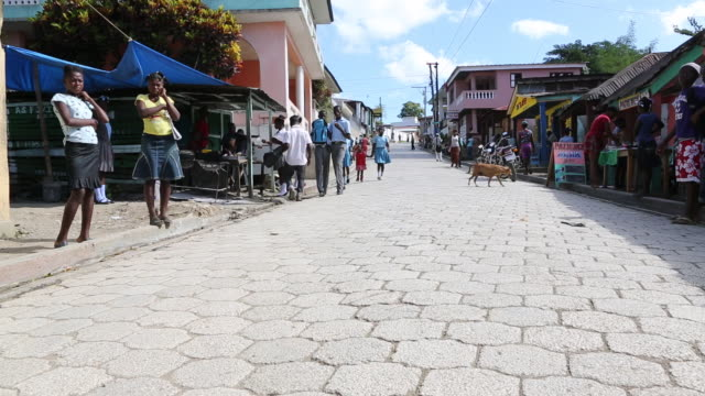 A wide angle shot of several young school girls in blue uniforms as they are walking down a busy street in Pilate Haiti while a young man on a moped...
