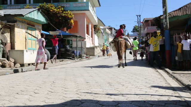 A wide angle shot of two young boys who are riding a donkey on a paved road in Pilate Haiti while two men on a moped are passing by