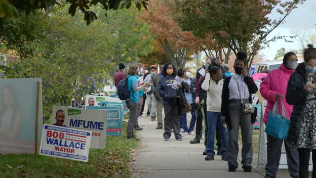 wide angle shot of voters line up to vote in the evening at barclay school in baltimore maryland - line stock videos & royalty-free footage