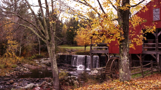 Wide angle shows old time water wheel, with waterfall in background.