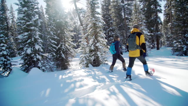 wide angle slow motion handheld tracking side view of adult hikers snowshoeing together outdoors in the snow with copy space - ski holiday stock videos & royalty-free footage