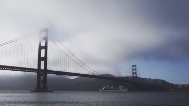 wide angle, static frame, complete span of golden gate bridge from fort point, marin headlands in background, fog rolls in, cruise liner steams out to sea - fog stock videos & royalty-free footage