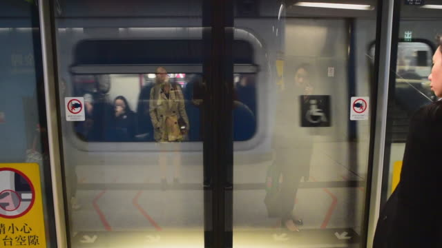wide angle: subway car comes to a stop as people wait to get on and off - hong kong stock videos & royalty-free footage
