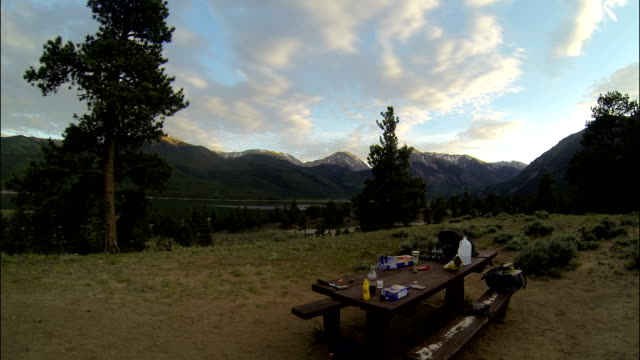 wide angle sunset rocky mountain camping picnic table sunset and mountains - picnic table stock videos and b-roll footage