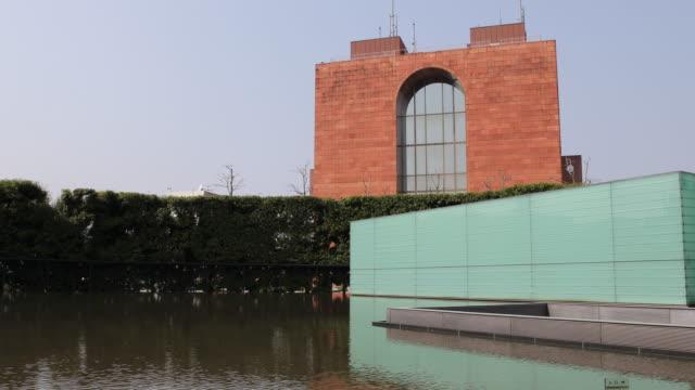 wide angle tilt up at the atomic bomb museum nagasaki entrance of the national peace memorial hall for the atomic bomb victims - massförstörelsevapen bildbanksvideor och videomaterial från bakom kulisserna