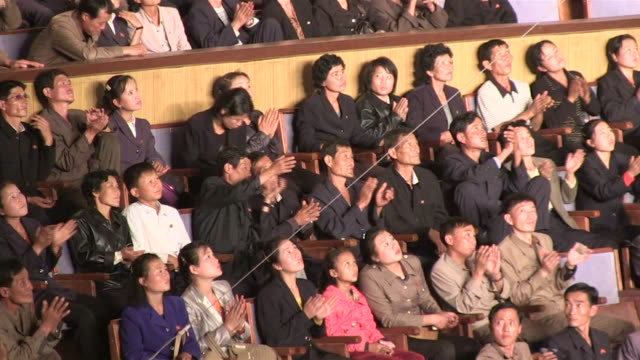 Wide angle view of a section of the audience stand in the Army Circus theater People giving an applause
