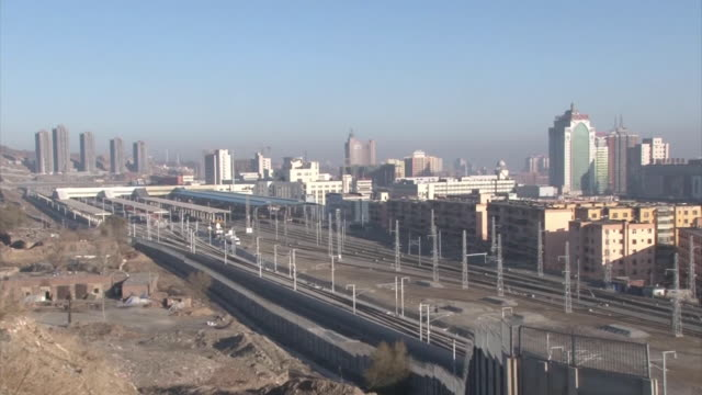 wide angle view of a train station and railroad tracks stretching across urumqi and skyscrapers in the city panning right to tall apartment buildings - schwenk stock-videos und b-roll-filmmaterial
