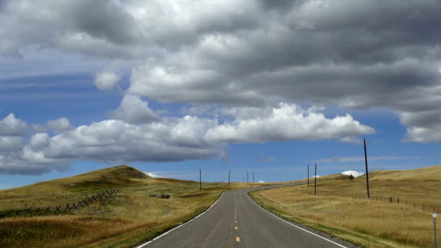 wide angle view of empty paved road with puffy clouds and blue sky with shadows rolling across landscape. - 消失点点の映像素材/bロール