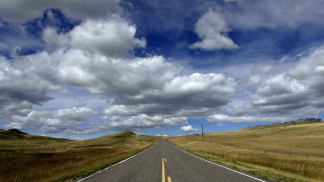 wide angle view of empty paved road with puffy clouds and blue sky with shadows rolling across landscape. - 30 seconds or greater stock videos & royalty-free footage