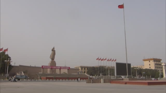 wide angle view of one of the main recreational places in kashgar renmin park a large statue of mao zedong with upraised arm looking over renmin park... - mao stock videos and b-roll footage