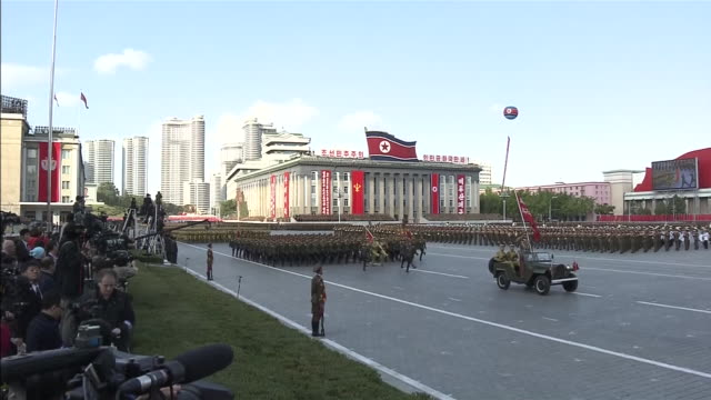 wide angle view of the north korean militay parade taking place at kim il sung square a military truck running through followed by a military march - military parade stock videos & royalty-free footage