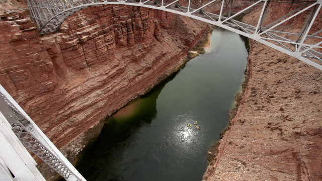 stockvideo's en b-roll-footage met wide angle view past steel bridge of yellow river rafts floating down deep red rock desert canyon. - colorado rivier