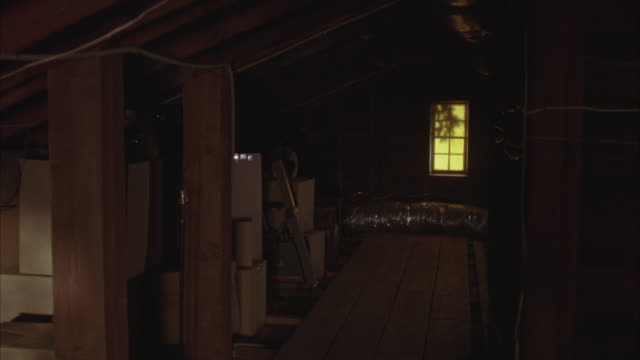 wide angle walking pov of attic. bare wooden walls and floor. wood planks. sunlight coming through windows. cardboard boxes stacked against wall. storage. - compartment stock videos & royalty-free footage