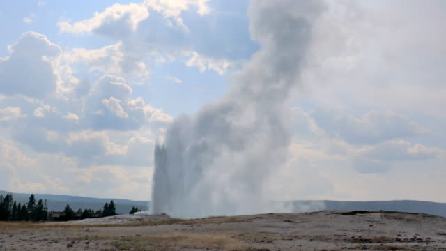 wide angle: water and steam flows high out old faithful geyser - geyser stock videos & royalty-free footage