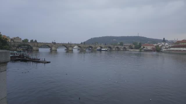 wide, arch bridge over vltara river in prague - osteuropäische kultur stock-videos und b-roll-filmmaterial