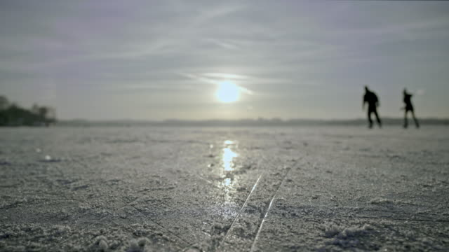 wide background shot of a frozen lake with the setting sun in background - frozen stock videos & royalty-free footage
