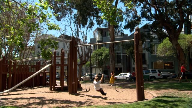 stockvideo's en b-roll-footage met a wide beauty shot of south park in san francisco california on a sunny day as people swing on swings and hang out in the park - schommelen bungelen