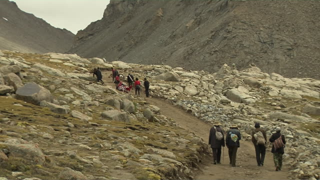 stockvideo's en b-roll-footage met wide block shot pilgrims doing circumambulation around mount kailash lhasa tibet china - bedevaart