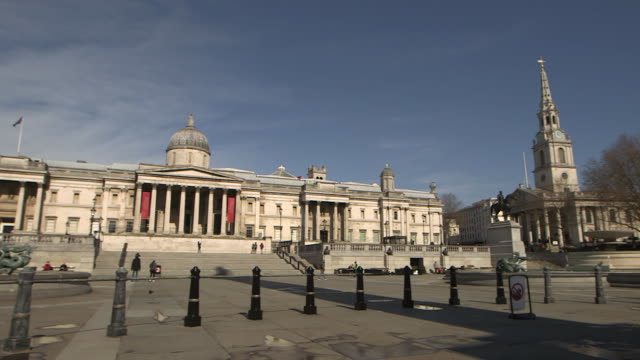 wide camera pan establishing shot of a nearly empty trafalgar square during the covid-19 pandemic in london. - healthcare and medicine or illness or food and drink or fitness or exercise or wellbeing stock videos & royalty-free footage