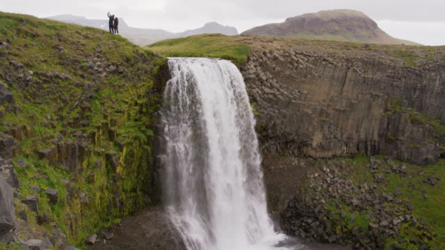 Wide crane shot of couple standing at edge of cliff near waterfall / Snaefellsnes, Iceland