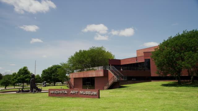 vídeos de stock e filmes b-roll de wide drive by exterior of wichita art museum - wichita