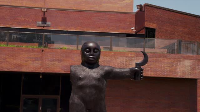 vídeos de stock e filmes b-roll de wide drive by exterior of wichita art museum with modern bronze art sculpture - wichita