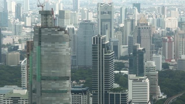 vídeos de stock e filmes b-roll de wide elevated shot, commercial and residential buildings stand in the sathorn district of bangkok, thailand, on tuesday, july 28 a crane operates on... - vista geral