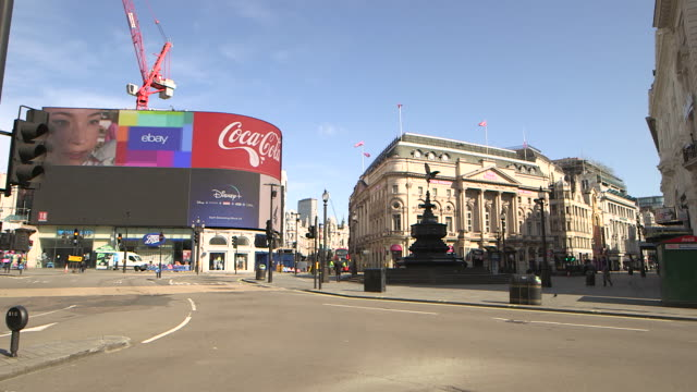 wide establishing shot of a nearly empty piccadilly circus during the covid19 pandemic in london england - fountain stock videos & royalty-free footage
