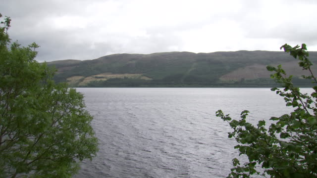 wide establishing shot of loch ness in scotland, united kingdom. - environment or natural disaster or climate change or earthquake or hurricane or extreme weather or oil spill or volcano or tornado or flooding stock videos & royalty-free footage