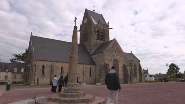 wide establishing shot of the church in sainte-mere-eglise, normandy. the monument to american paratrooper john steel is seen on the church steeple. - steeple stock videos & royalty-free footage