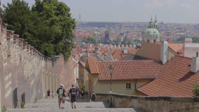 wide establishing shot of tourists walking on the steps besides prague castle against a backdrop of the city - hradcany castle stock videos & royalty-free footage