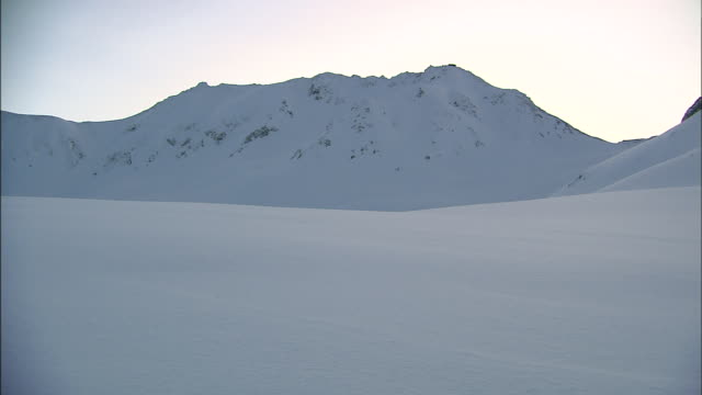 a wide expanse of snow gives way to mt. tateyama in murodo, japan. - satoyama scenery stock videos & royalty-free footage