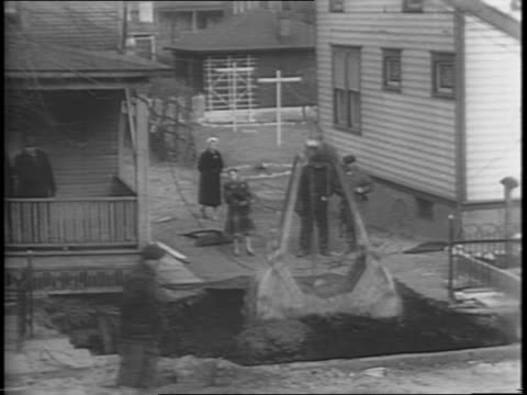 Wide exterior shot of men and police standing around a large hole in front of a house as a coal mine shaft below the sidewalk gave away and a two...