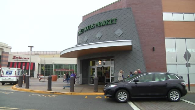 a wide exterior shot of the entrance of a whole foods market store on a rainy day in paramus new jersey as customers enter and exit a zoom out shot... - whole foods market stock videos and b-roll footage