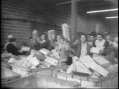 Wide exterior view and pan of post office in Long Island / medium shot of train arriving at post office / wide interior shot of people sorting mail /...
