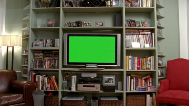 vídeos de stock, filmes e b-roll de ws wide flat screen television set up on bookcase in room, new york city, new york, usa - esetante de livro