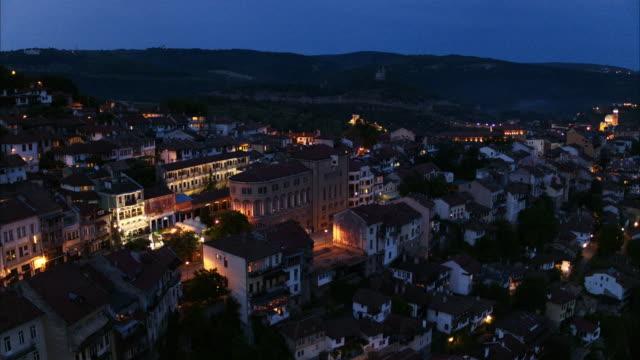 vídeos de stock, filmes e b-roll de wide flyover shot approaching houses on hillside at night / veliko tarnovo, bulgaria - bulgária