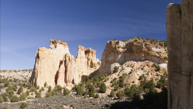 Wide flyover shot of rock formations in desert / Cannonville, Utah, United States