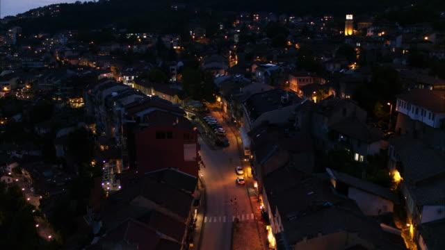 wide flyover shot of street on urban hillside at night / veliko tarnovo, bulgaria - 住宅点の映像素材/bロール