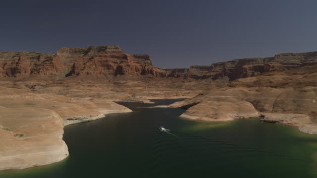 wide flyover view of boat in lake near mountains / lake powell, utah, united states - lago powell video stock e b–roll