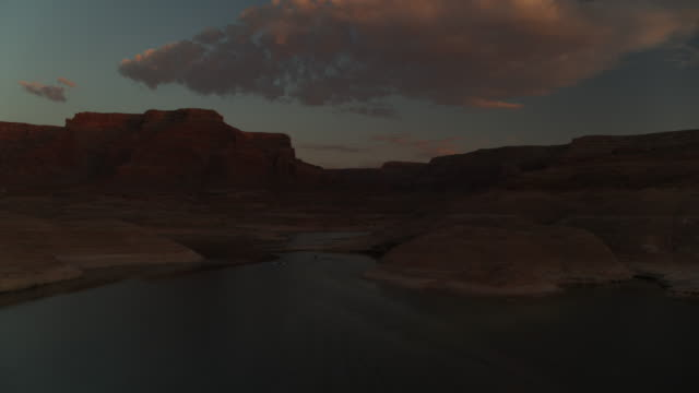 wide flyover view of jet boats on mountain lake at sunset / lake powell, utah, united states - lake powell stock-videos und b-roll-filmmaterial