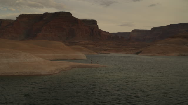 vidéos et rushes de wide flyover view of passing women on shore of lake near mountains / lake powell, utah, united states - lac powell